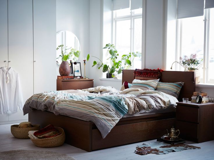 A light medium sized bedroom furnished with a brown bed for two combined with bedside tables and a chest of drawers.