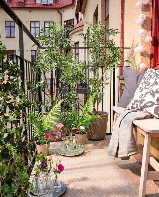 Crea un jardín en el balcón sin tener que plantar nada; sólo necesitas unos tejidos y plantas y flores artificiales.