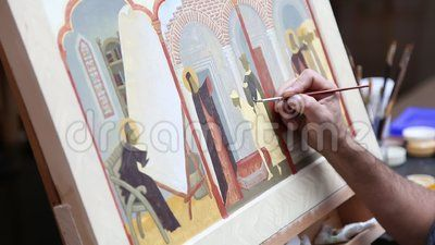 Iconographer painting - brush in hand man.