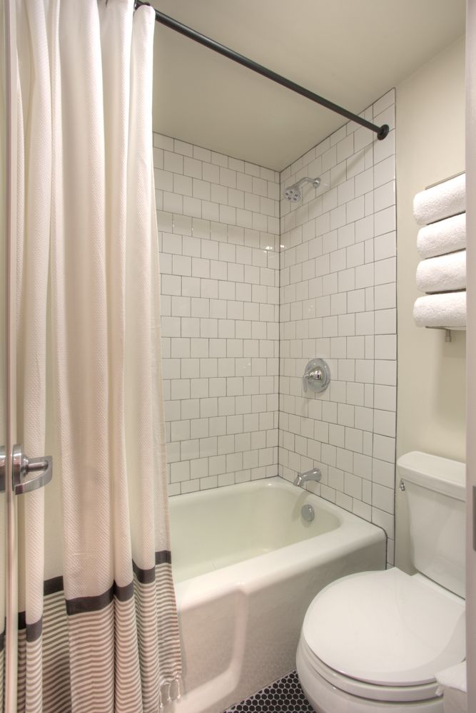 hotel durant white 4x4 tile with gray grout black powdered coated rod iron shower rings