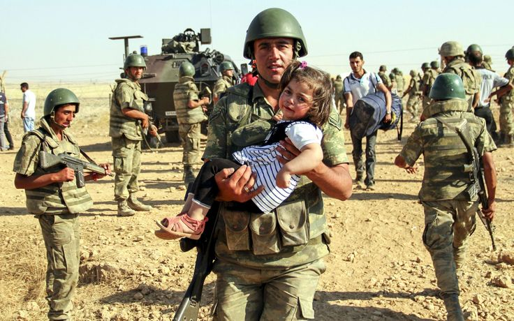 2015 Monday, June 8: Turkish Border       A Turkish soldier carries a Syrian girl as she crosses into Turkey with her family on June 06, 2015. Hundreds of Syrians fleeing clashes between Syrian government