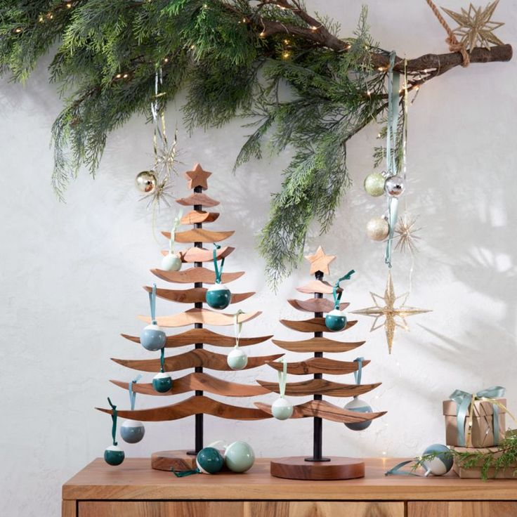 Prelit branch and Scandi Christmas trees with blue accents.