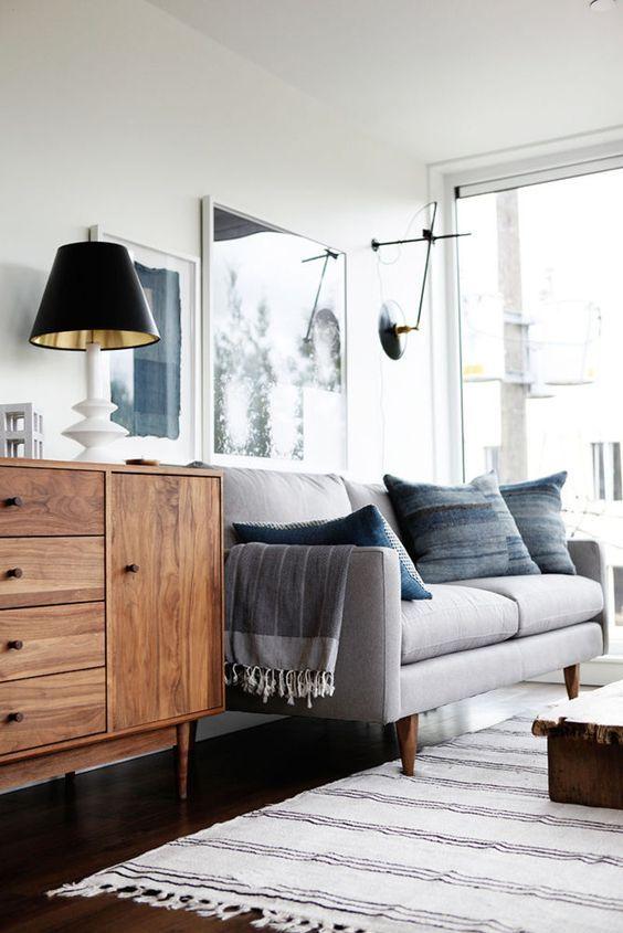 Großes, helles Wohnzimmer in Grautönen und schöner Holzkommode
