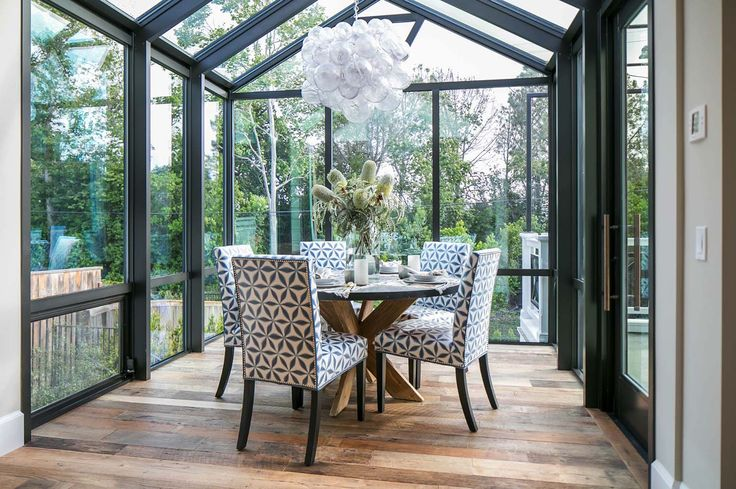 A solarium features a cozy breakfast nook with vinyl covered chairs and an eye-catching chandelier over the zinc-clad dining table. The cast resin chandelier is in the form of several bubbles clumped together to create a unique art form. Source:  Muriel Chandelier from Oly Studio.