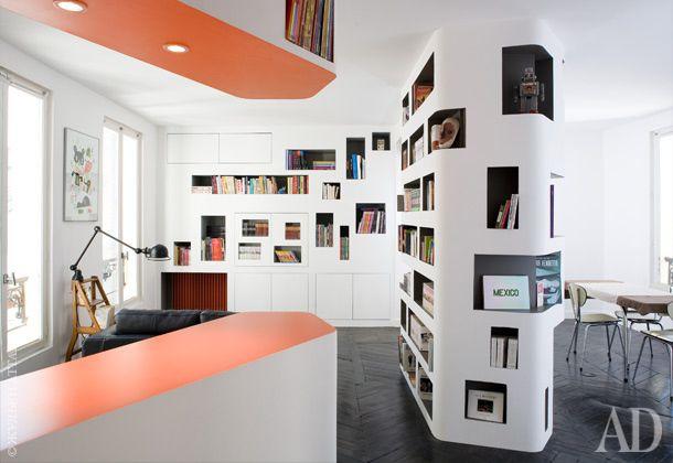 Гостиная в парижской квартире. От столовой комната отделена стеной, превращенной в стеллаж. Телевизор и прочая аудио- и видеотехника спрятаны в стенные шкафы.