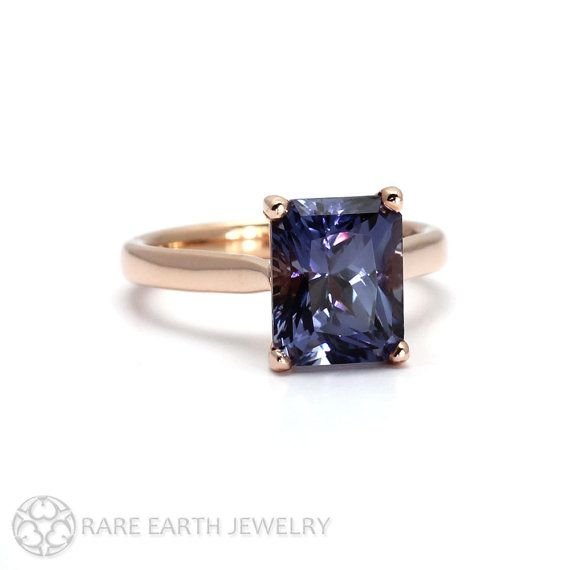 An absolutely gorgeous color change Sapphire solitaire ring. At the center is a 4.75ct lab grown radiant emerald cut color change Sapphire set in a
