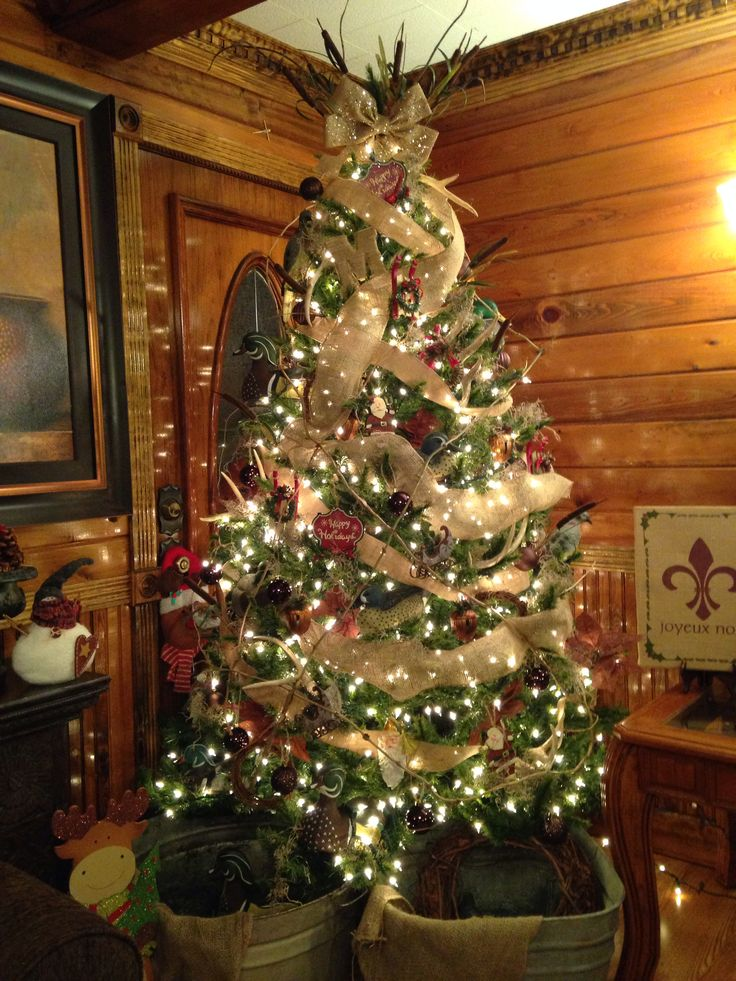 Christmas tree with deer antlers, decoys, burlap, cat tails, twigs