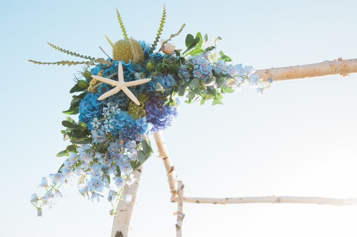 Seaside Whimsy Wedding: Ceremony Structure with Blue Flowers and Shells. The florals for this wedding combined feminine blooms with textural and architectural elements reminiscent of the sea. Sea stars and King Protea anchor this arrangement with Nigella and Coxcomb celosia providing texture. Hydrangea stands out as a vivid blue against the brick structure accented by more subtle tones of eucalyptus, delphinium, and tweedia.