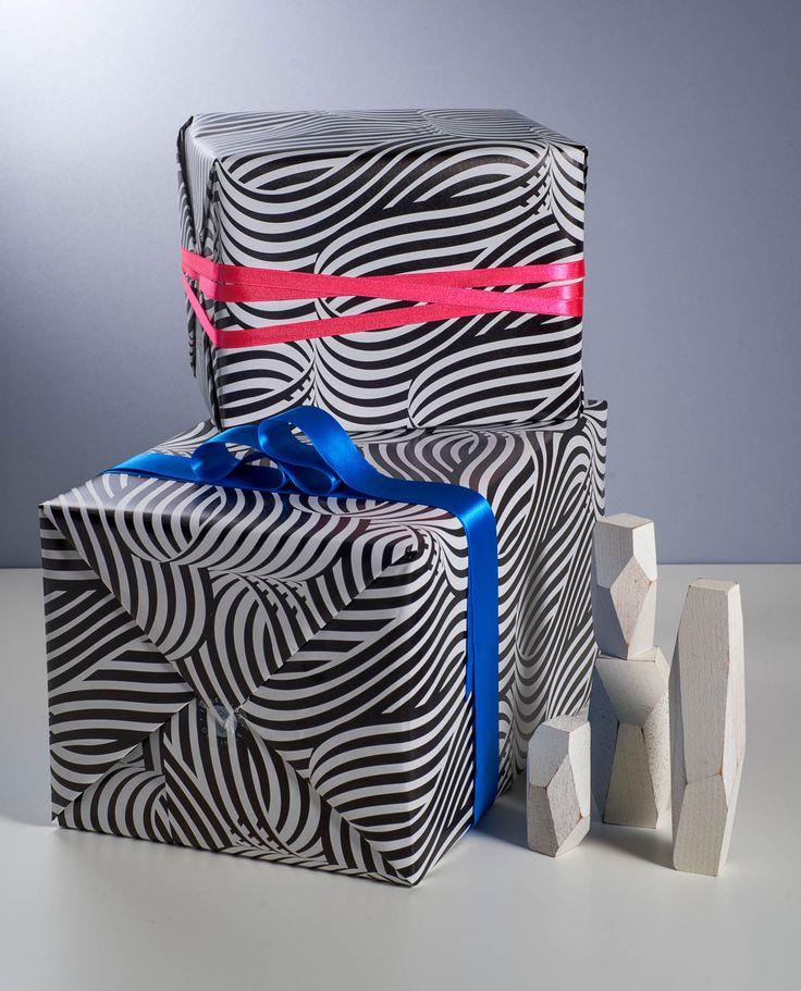 """MattChase  """"Vague Optique""""papier cadeau Le motif s'inscrit dans le mouvement de l'op-art (ou art optique) dont Bridget Riley et Victor Vasarely en sont les porteurs de lance. L'esthétisme abstrait d'une forme simple créé la sensation d'un mouvement perpétuel. L'objectif du dessin est de remettre en question celui qui regarde. Ce papier séduira les âmes joueuses et les goûts arrêtés."""