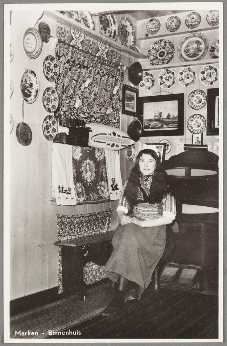 Vrouw in Marker dracht poseert in een interieur. Op de rand van de bedstede een oranje doek met afbeelding van koningin Wilhelmina en geborduurde kussens. 1935-1955 #NoordHolland #Marken