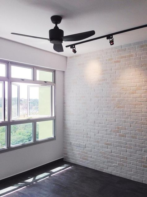 brick textured wall with track lighting on ceiling in living room