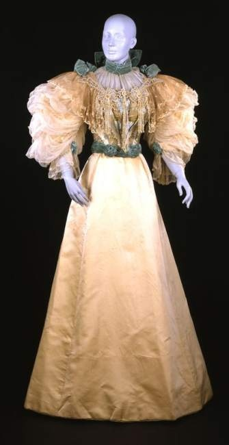 """Circa 1896 Evening dress, the John Shillito Co., Cincinnati. Leg-of-mutton sleeves, an S-shaped silhouette achieved with a tightly corseted bodice, a wide skirt, pastel colors, and elaborate trimmings of lace, beads, and velvet ribbon. The """"demitoilette,"""" with its enclosed neckline and covered upper arms, was appropriate for evening gatherings that did not include dancing. Ball gowns, as opposed to evening dresses, were generally décolleté, with a low neckline and bare shoulders."""
