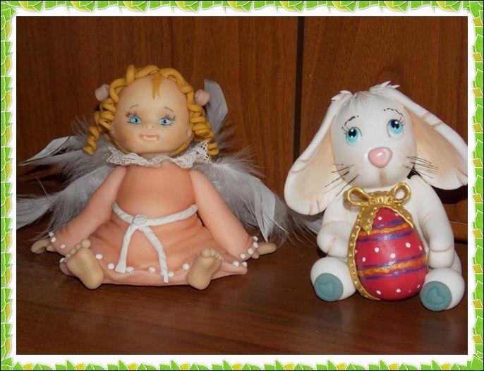 angelo seduto e un coniglietto con il suo uovo di Pasqua