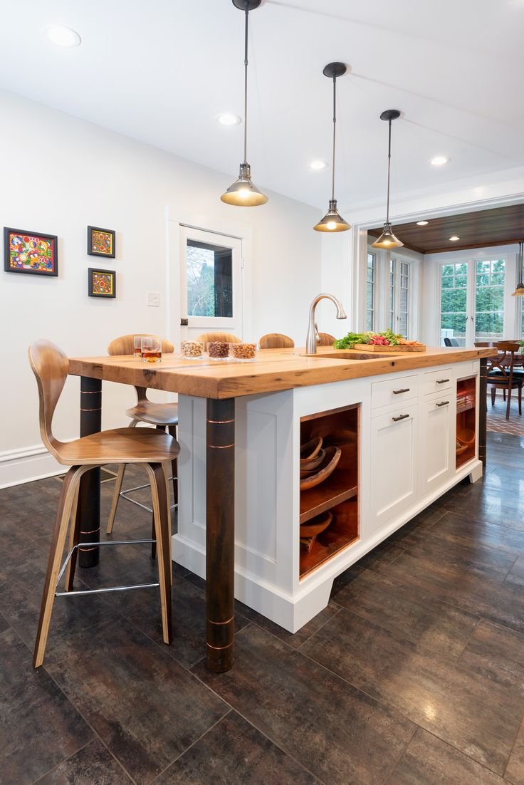 The white cabinetry, wooden legs, and wooden top of this island tie in perfectly to this industrial kitchen design. Follow us and check out our website's gallery to see the rest of this project and others!