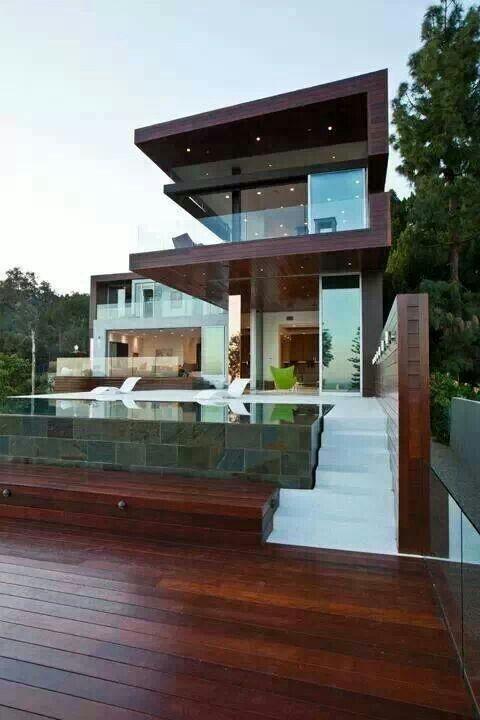 Prachtig modern strak met huis geintegreerde tuin met donker hout en open constructies.