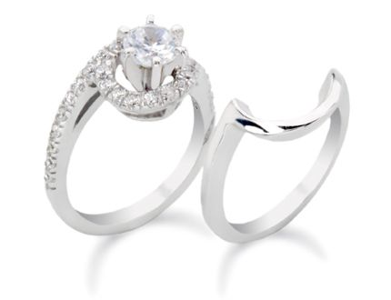 White gold engagement ring featuring a round diamond in a six prong setting surrounded by round melee.
