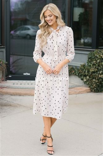 Beautiful blush polka dot dress with 3/4 length sleeves, v neck and ribbon neck tie, gathered elastic waist and black brush stoked print.