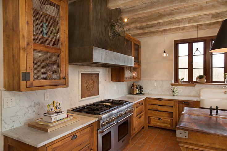 Дизайн кухни в деревенском стиле: массивная вытяжка над плитой