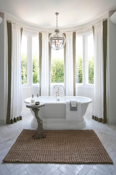 A marble herringbone tiled floor leads to a bow window dressed in white and taupe curtains filled with a roll top bathtub and a faux bois accent table illuminated by a Restoration Hardware Victorian Hotel Pendant.