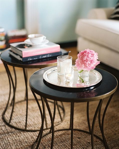 Living Room Photo - A pair of side tables styled with flowers, candles, and books
