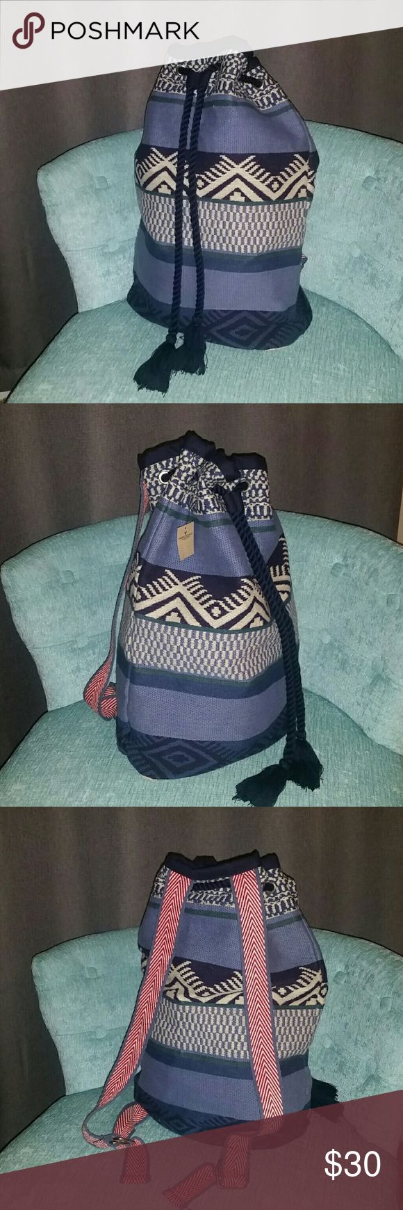 AMERICAN EAGLE BOHO TAPESTRY BOOK BAG KNAPSACK American Eagle tribal print boho knapsack style book bag. This is made of a thick tapestry or blanket like material. The material is done in shades of blue and ivory with a few green stripes. The straps are a coordinating red and ivory with blue trim and they are adjustable. It has navy blue soft rope pull closure. Inside is a solid navy cotton blend material with two slip pockets on the back wall.  19 x 15 x 5 American Eagle Outfitters Bags…