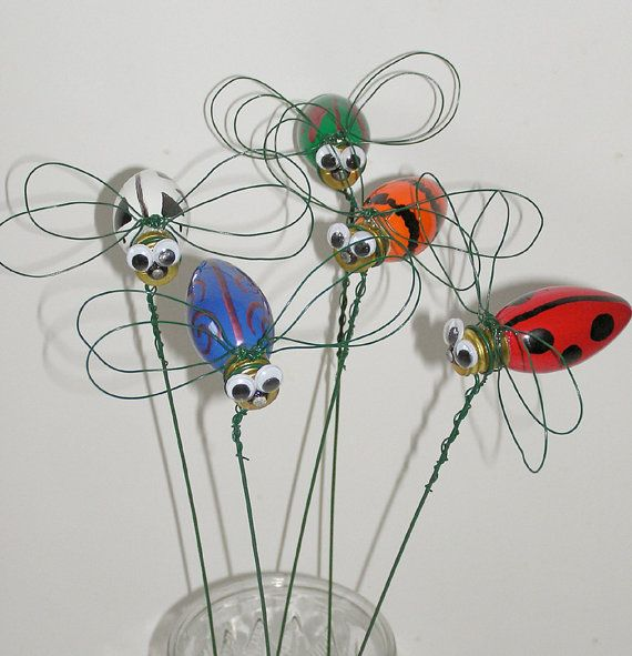Garden stakes made from recycled Christmas light bulbs and wire. Also cute to use metal washers for eyes (wired on) and yellow Christmas bulb to make a lighting bug insect