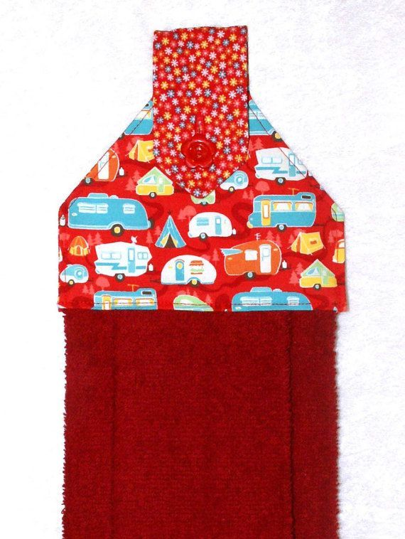 A red hand towel with cheerful campers and flowers. The plush red towel is more luxurious than a standard kitchen towel. Featuring a designer fabric of campers on red and a coordinating red floral fabric fabric, it is sure to add fun to your home or camper kitchen.  This handmade hanging towel works well buttoned over the handle of stove, dishwasher, drawer pull, or even a knob, door knob or vertical handle with optional hanging ring. It can even be used over a towel bar in the bathroom or…