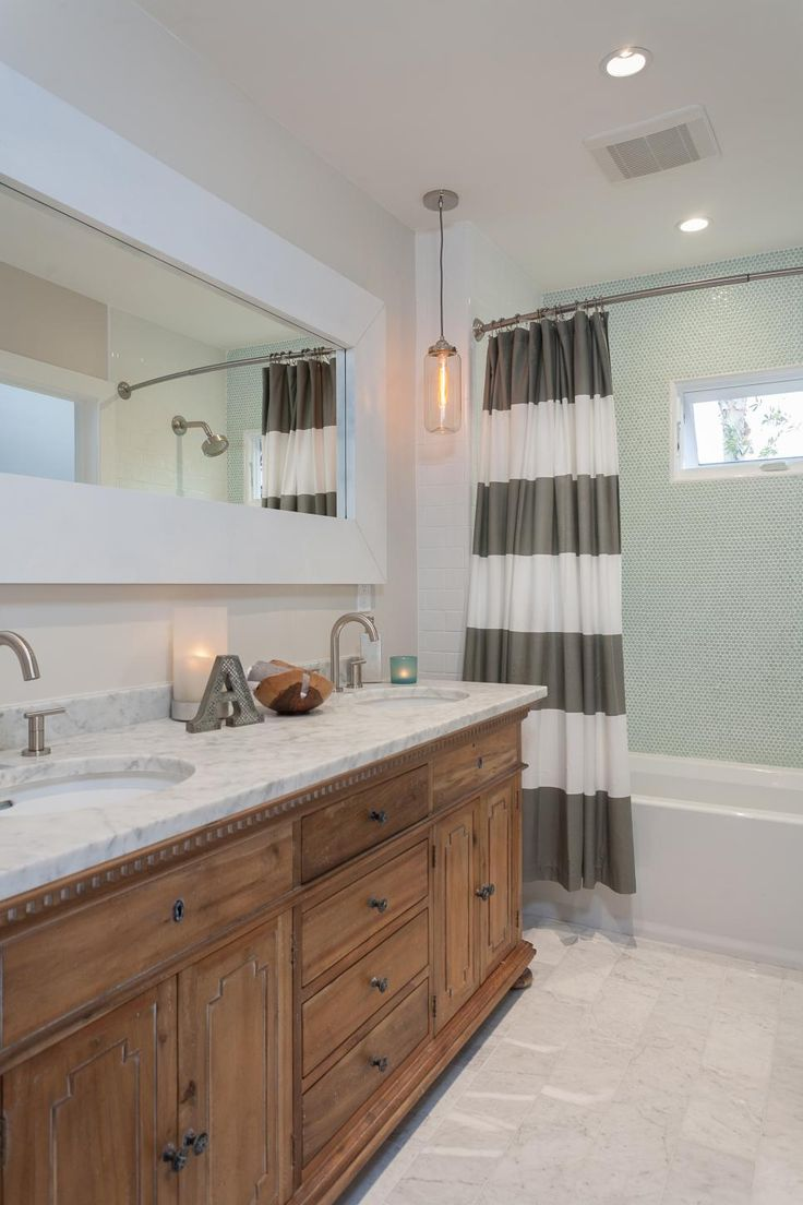 In the bathroom, a Southwestern-style wood vanity gets topped with white marble for an extra luxurious touch. The shower features pale blue mosaic tile that glitters under the lights.
