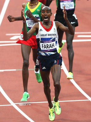Mo Farah of Great Britain celebrates as he crosses the finish line to win gold ahead of Dejen Gebremeskel of Ethiopia in the men's 5,000 meters.