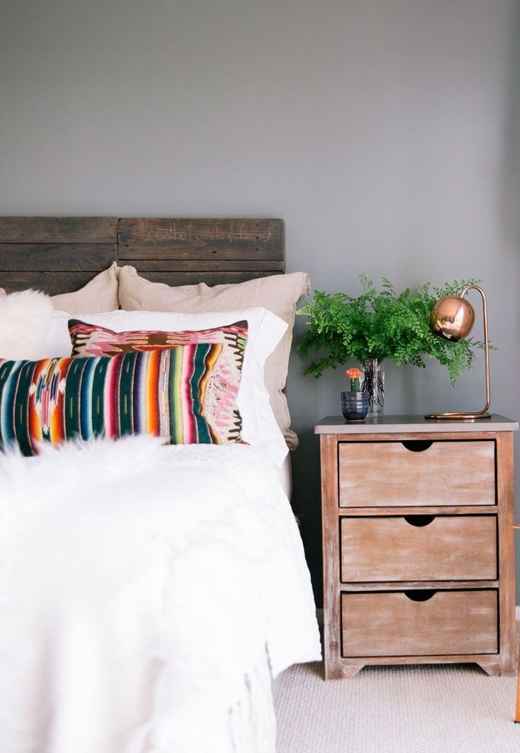 Keep your bedroom feeling natural with light bedding, reclaimed wood furniture, and something green on your nightstand. That's just one of the genius decorating ideas from this stunning home tour...