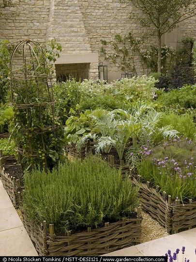 I love the woven enclosures - I think it's called hurdling- in this beautiful garden.  I believe it is a potager, that is, kitchen garden.