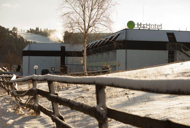 Im Vordergrund der eingeschneite Weidezaun - Im Hintergrund einen Hang, welcher zum Skifahren einläd | H+ Hotel Willingen