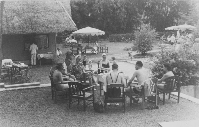 """Badgasten zittend op stoelen in een halve kring naast het zwembad Dago te Bandung, Java. Op de achterzijde staat meermalen gedrukt: """"Fotohuis Braga"""" D.E.N.I.S. Gebouw Bandoeng.. Date 1940 Source: Tropenmuseum"""