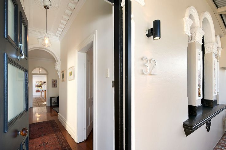 Wide central hallway w classic archway. High ornate ceilings, polished floorboards.