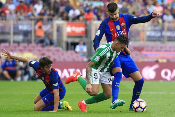 Barcelona's defender Gerard Pique (Up) vies with Betis' Paraguayan forward Antonio Sanabria during the Spanish league football match FC Barcelona vs Real Betis Balompie at the Camp Nou stadium in Barcelona on August 20, 2016. / AFP / PAU BARRENA