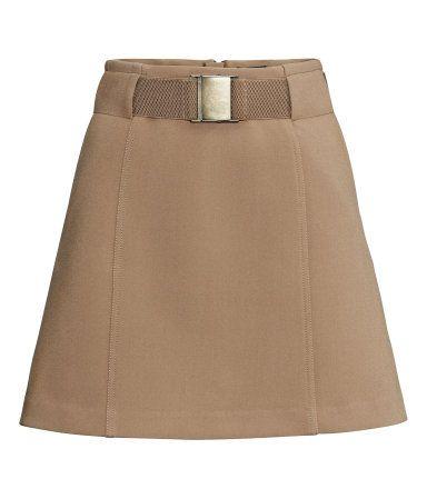 Falda corta en tejido elástico de crepé. Cinturón elástico a juego con hebilla de metal y cremallera visible detrás. Sin forrar.