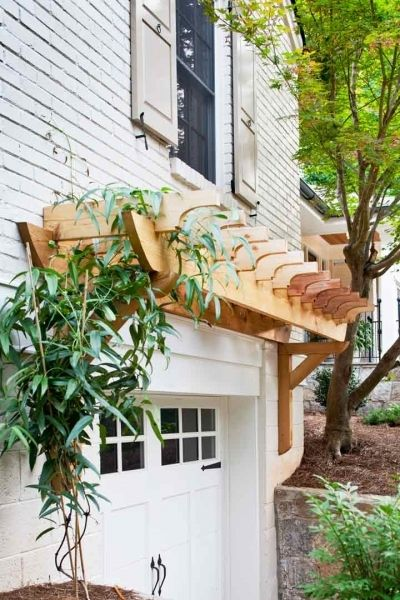 Simple pergola over garage door. I have thought about doing this before to our house and now after seeing it done, I really love the idea.