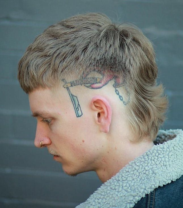 Blonde Wavy Mullet Is This A Blend Between Less Maintenance And Funky The Sides Are Faded To Bring The Tattoo In 2020 Mullet Haircut Mullet Hairstyle Modern Mullet