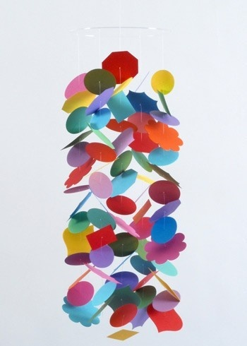 This gracefully designed mobile will bring a poetic and modern charm to a childs room or nursery. The Confetti mobile in a burst of rainbow colors is handmade from card stock paper and die cut into a variety of shapes. The shapes are artistically strung on strong clear thread and hang from a thin acrylic disc; an extra length of thread is included to hang the mobile at desired height. Comes packaged flat in a lovely envelope which makes for an elegant gift presentation. Crafted in the USA.