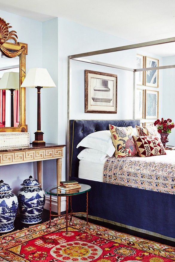 Antique style bedroom with patterned textiles and velvet tufted headboard.