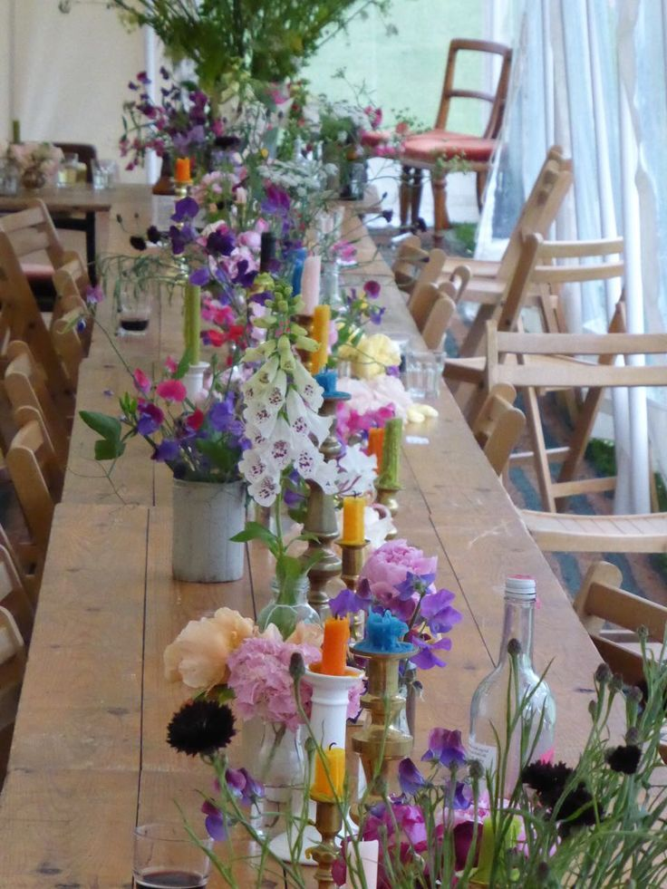 coloured candles and flowers in vintage mismatched vessels - English country wedding