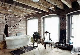 Urban bathroom with exposed brick walls and ceiling. Old light floors and big spacious windows that let lots of light in. Interesting antler art on wall for towels and bathrob.