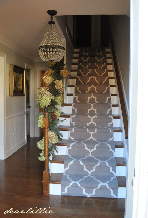 Lovely foyer with stair runner Lovely way to decorate the banister for Spring/Summer too!