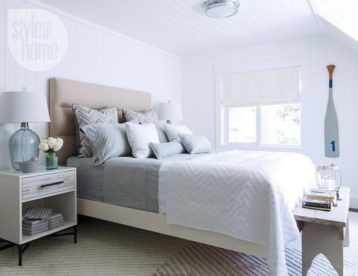 Beautiful monochromatic bedroom features West Elm Panel Tufted headboard on queen bed layered with gray sheets, gray chevron pillows and a white chevron coverlet, flanked by West Elm Wood Tiled Nightstands topped with blue glass bottle table lamps atop a West Elm Chevron Knot rug with gray farm bench at the foot of the bed. The bedroom walls and ceilings are clad in tongue and groove with a nickel flush mount ceiling light.