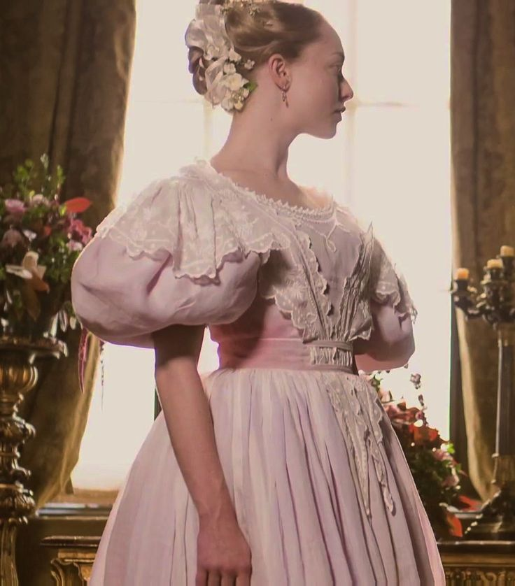 Les Misérables (2012) - Amanda Seyfried as Cosette wearing a pink dress with short puffy sleeves, round neckline and white embroidered muslin overlay on the bodice and sleeves.  The costumes were designed by Paco Delgado