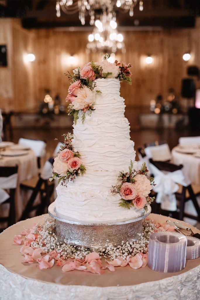The prettiest, blush pink, bohemian wedding cake. Love the layered frosting, fresh blooms, and petals surrounding the base. Such a natural way to dress up your bohemian wedding cake! Photo taken at THE SPRINGS Event Venue. Follow this pin to our website for more information, or to book your free tour! SPRINGS location: Edmond, OK Photographer: Kelcy Leigh Photography #weddingcake #weddingcakeideas #bohowedding #bohoweddingcake #bohemianwedding #bohemianweddingcake #blushwedding…