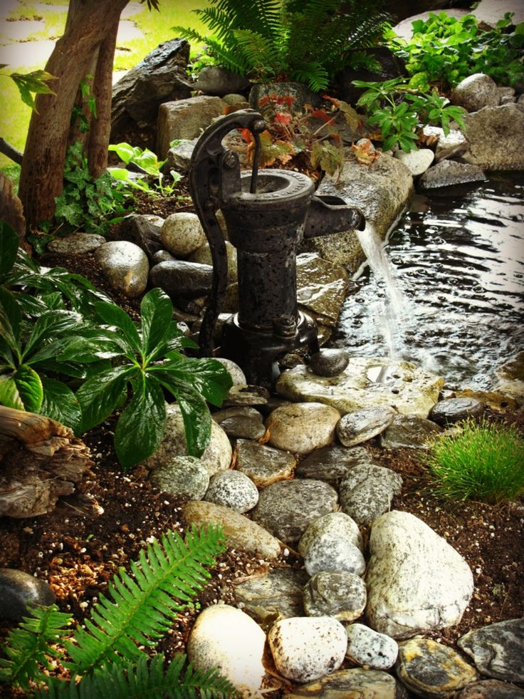 Vintage hand water pump repurposed as a water feature/fountain.