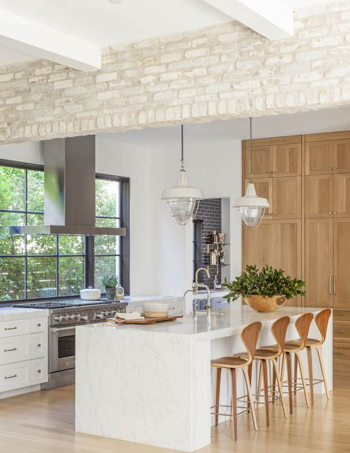 exposed light brick, window around range.... add a back splash for cleaning purposes in the middle behind work area but have window on side and top. Sink across with lots of prep space