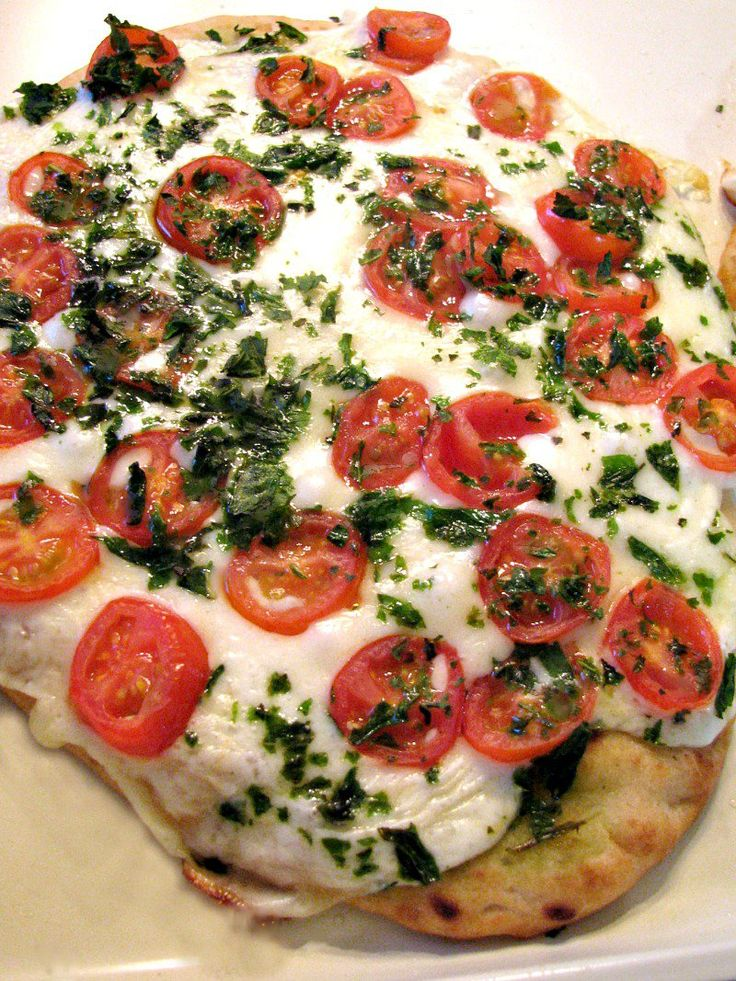 Naan flatbread topped with mozzarella cheese slices, sweet cherry tomatoes, basil, and olive oil. This Margherita Naan Pizza is incredibly easy to make and ready in about 20 minutes.