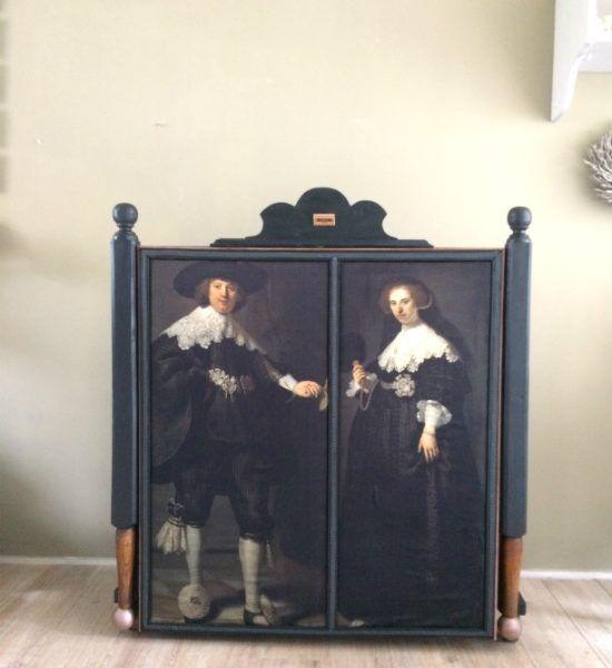 """Love Seat met verhaal Deze bijzondere Love Seat is gemaakt van een 19e eeuws boeren bed. Zijn stoere zwarte kleur maakt hem spannend en sluit mooi aan op de door Rembrandt geschilderde portretten van Marten en Oopjen die op satijngeweven katoen zijn geprint.  Doordat dit mooie bankje is voor zien van oude, industriële en massief ijzeren zwenkwielen, extra hoog is en mooie portretten van """"Marten & Oopjen"""" kan hij mooi als """"roomdivider"""" fungeren."""